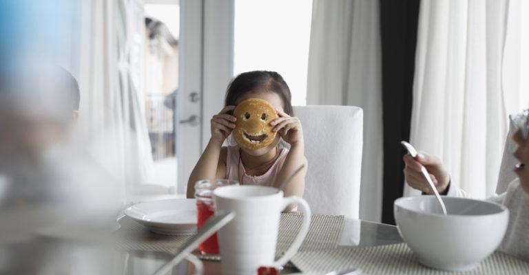 Portrait girl holding pancake smiley face at breakfast table