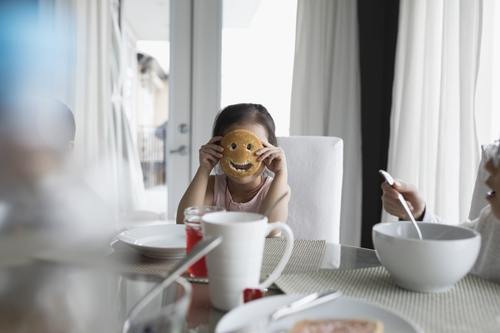 Portrait girl holding pancake smiley face at breakfast table