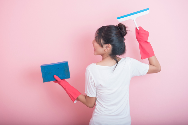 Beautiful asian housewife smiling on pink background