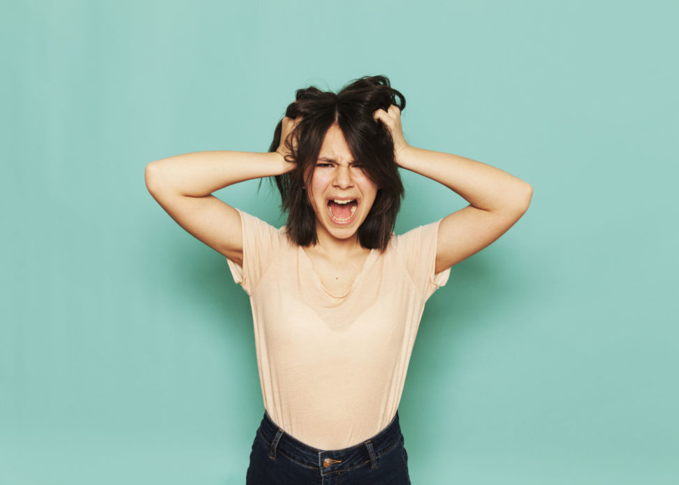 Portrait of frustrated girl shouting with hands in hair against turquoise background