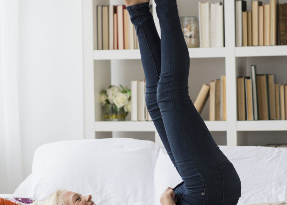 Woman putting on skinny jeans on bed, Jersey City, New Jersey, USA