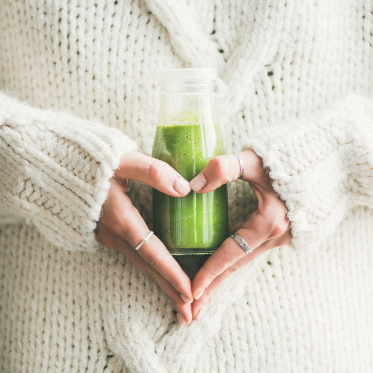Winter seasonal smoothie drink detox. Female in sweater holding bottle of green smoothie or juice making heart shape with her hands, square crop. Clean eating, weight loss, healthy dieting food concept