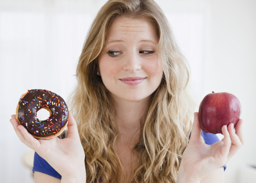 USA, New Jersey, Jersey City, Young woman choosing between donut and apple