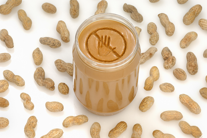 A concept photograph of a no entry or prohibited sign engraved into a jar of peanut butter.  Ideal for peanut allergy warnings.