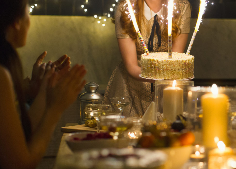 Enthusiastic woman serving cake with sparkler fireworks to clapping friends