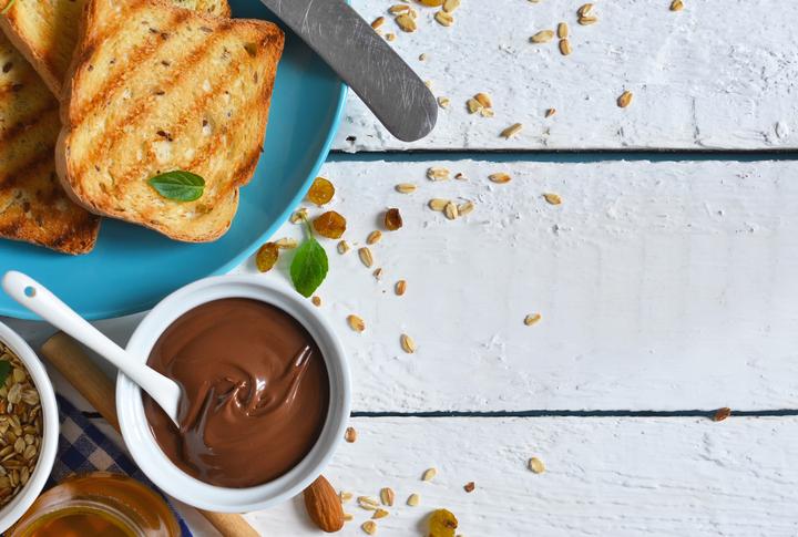 Good morning - toast with Nutella, banana and honey. White food background.