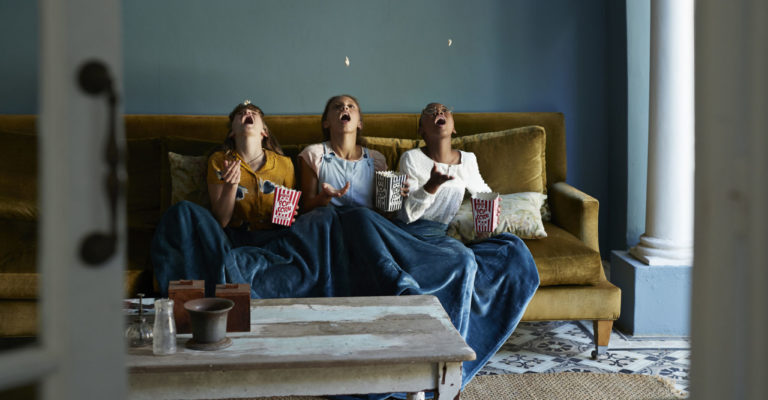 Tween girls hanging out and eating popcorn together in bohemian style home